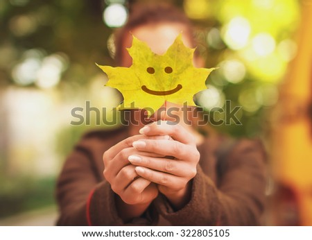 smile on autumn maple leaf in woman hands - stock photo