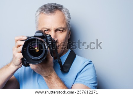 Smile! Portrait of confident senior man in T-shirt holding camera while standing against grey background
