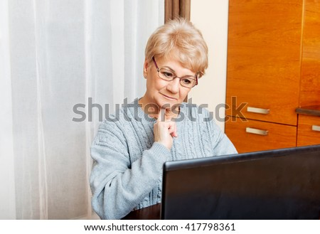 Smile senior sitting at table and using laptop - stock photo