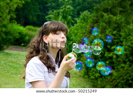 smile teen with soap bubbles in vivid green spring forest park