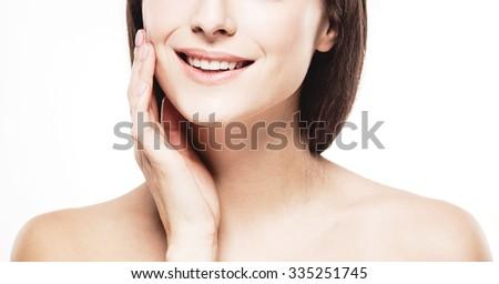 Smile teeth hand neck Beautiful woman face close up portrait studio on white - stock photo