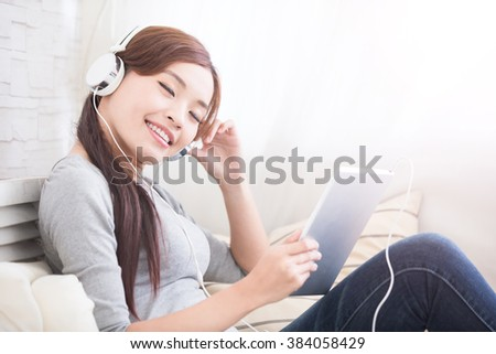 smile woman listen to music in digital tablet on sofa, asian beauty - stock photo