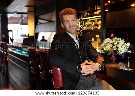 Smile young man in a black suit at the bar - stock photo