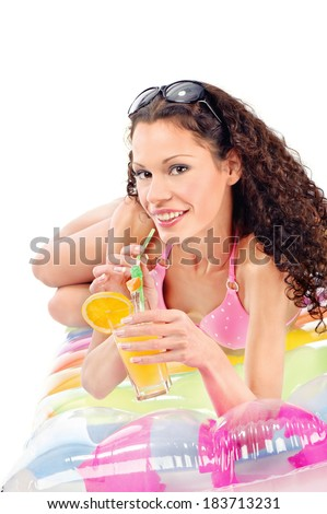 Smiled curl girl drink juice on air mattress, isolated on white - stock photo