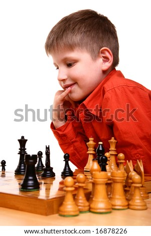Smiled little blond boy in orange shirt thinking deep while playing chess game - stock photo