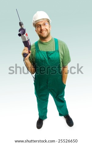 Smiled workman in helmet and overalls with drill on white background - stock photo