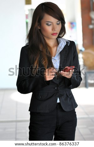 Smiles of young Asian businesswoman using handphone