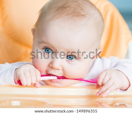 smiley baby girl is holding a spoon in his mouth and going to eat