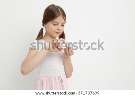 Smiley beautiful caucasian little girl and cosmetic creme