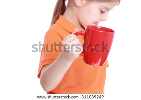 Smiley beautiful little girl drink tasty red tomato juice on Food and Drink theme - stock photo