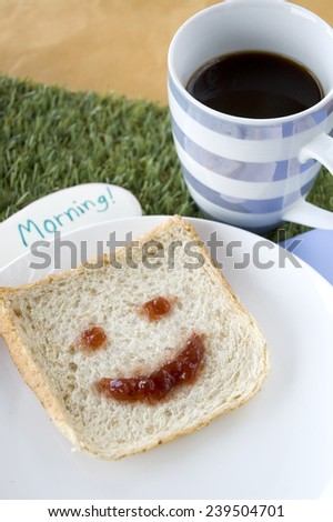 smiley bread and coffee with morning note for breakfast - stock photo