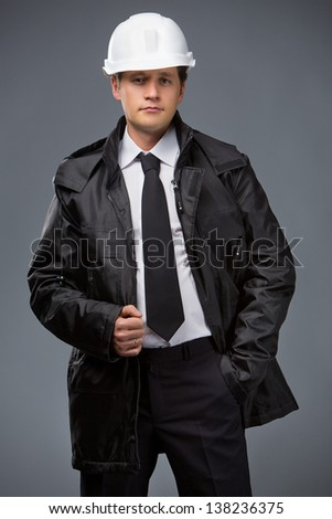 Smiley builder in a black suit jacket and white helmet - stock photo