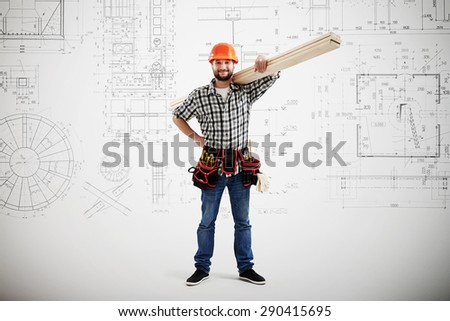 smiley builder in uniform holding long wooden boards over grey wall with prints - stock photo