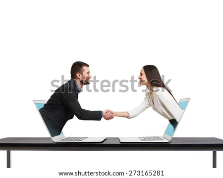 smiley businessman and businesswoman come out from laptop, shaking hands and looking at each other over white background - stock photo