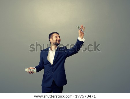smiley businessman holding paper money over dark background - stock photo