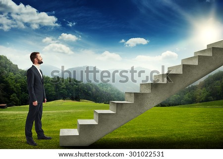 smiley businessman standing on the green meadow and looking up to the stairs - stock photo