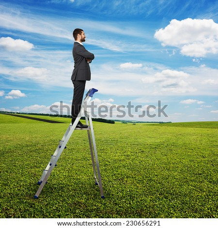 smiley businessman standing on the pair of steps and looking forward. photo at outdoor - stock photo
