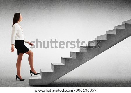 smiley businesswoman in formal wear walking up concrete stairs over light grey background - stock photo