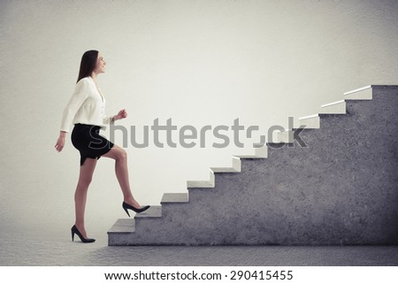 smiley businesswoman in formal wear walking up stairs over light grey background - stock photo