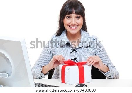 smiley businesswoman pack up small present at her workplace - stock photo
