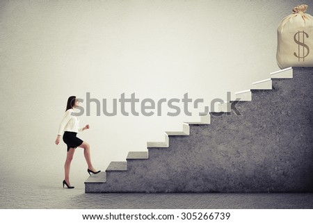 smiley businesswoman rising up stairs and looking at big bag with money on the top over grey background - stock photo