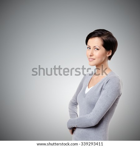 Smiley cheerful woman, on grey background - stock photo