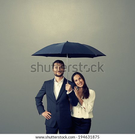 smiley couple under umbrella over dark background - stock photo