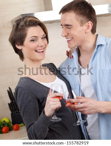 Smiley couple with glasses embraces one another in the kitchen