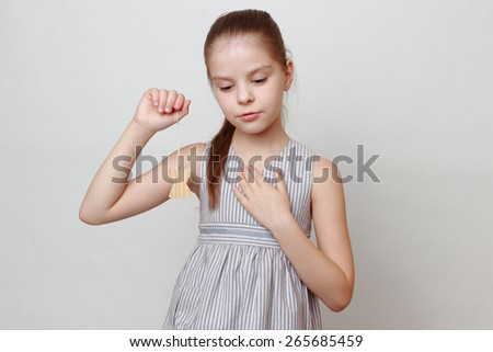 Smiley european little girl holding wooden angel on Christmas holiday - stock photo