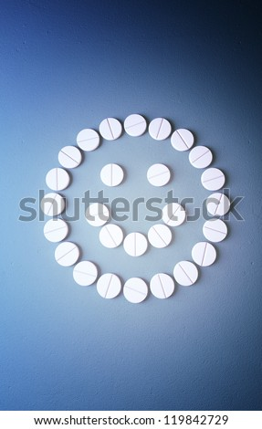Smiley face from pills on blue background - stock photo