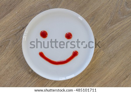smiley face of tomato source on white plate over wooden background