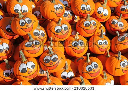 Smiley faces painted on fresh Pumpkins in the Autumn - stock photo