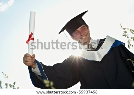 smiley graduate student in cloak holding a diploma over his head outdoors with sun back light