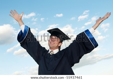 smiley graduate student in cloak with open risen arms ourdoors - stock photo