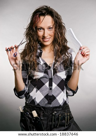 smiley hairdresser with tools against grey background - stock photo