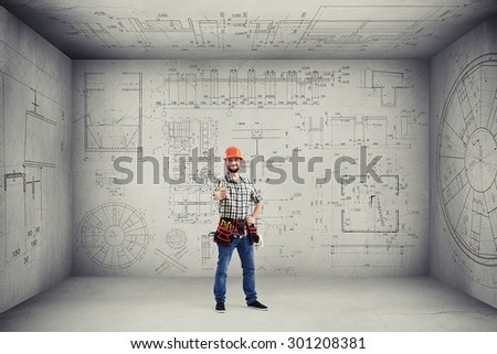 smiley handyman with tools on the belt showing thumbs up and standing in empty room with prints on the walls and ceiling - stock photo