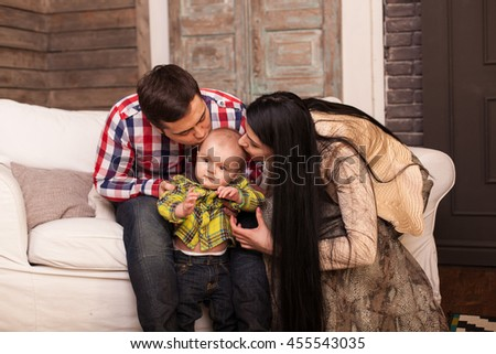 smiley happy family sitting on the sofa at home, mum, dad and their child son toddler fooling around - stock photo
