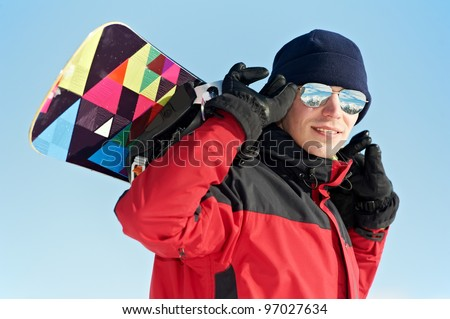 smiley happy sportsman with snowboard at winter outdoor - stock photo