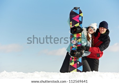 smiley happy young sportswoman and sportsman with snowboard at winter outdoor - stock photo