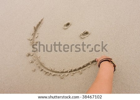 Smiley in the sand at the beach - stock photo