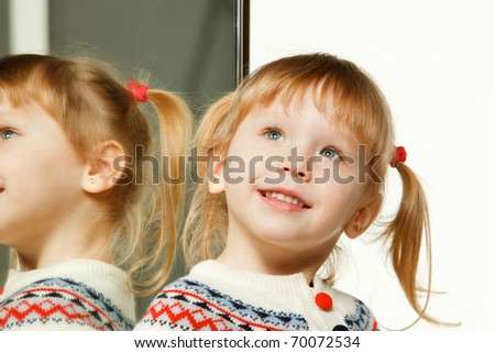 Smiley kid looking up standing near the mirror - stock photo