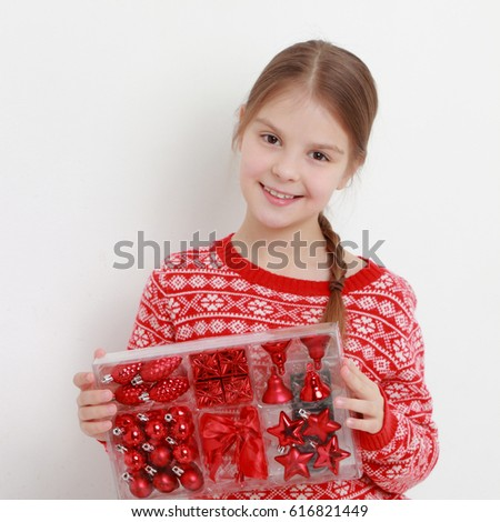 Smiley kid wearing beautiful red sweater and holding Christmas decoration