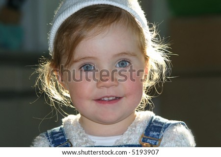 Smiley little girl in white hat over defocused background
