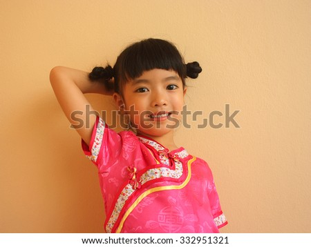 Smiley little girl standing at wall background, selective focus - stock photo