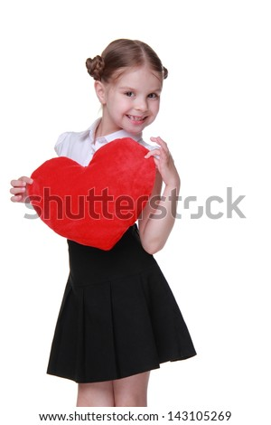 Smiley little  schoolgirl wearing white blouse and black skirt and holding red love symbol