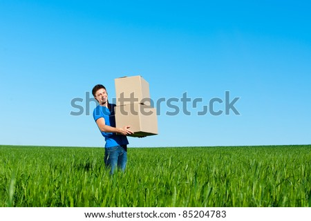 smiley man in blue t-shirt carrying boxes - stock photo
