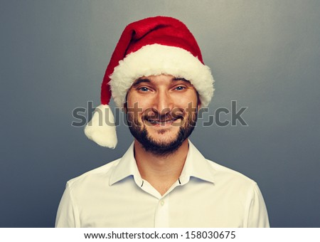 smiley man in santa claus hat over grey background