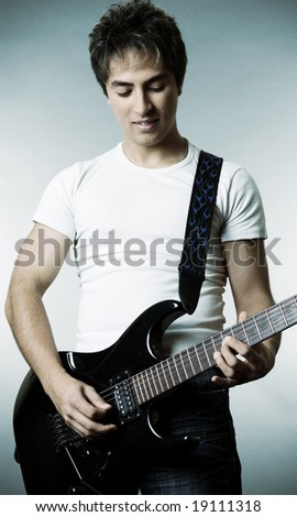 smiley man with guitar over grey background - stock photo