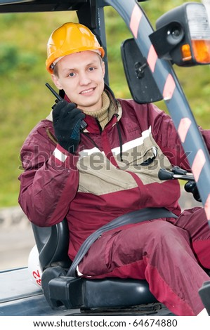 smiley man worker sitting in industrial stacker at warehouse using radio transmitter - stock photo
