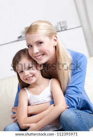 Smiley mother embraces her lovely daughter - stock photo
